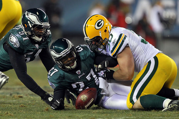 PHILADELPHIA, PA - JANUARY 09:  John Kuhn #30 of the Green Bay Packers fights for a fumble against Quintin Mikell #27 and Jamar Chaney #51 of the Philadelphia Eagles during the 2011 NFC wild card playoff game at Lincoln Financial Field on January 9, 2011