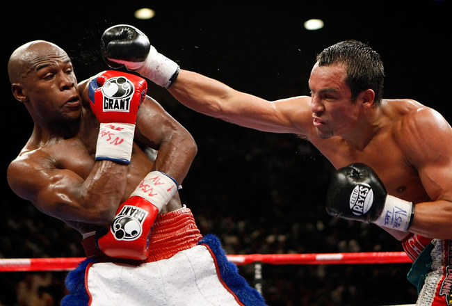 LAS VEGAS - SEPTEMBER 19:  Floyd Mayweather Jr. (L) dodges a punch from Juan Manuel Marquez in the fifth round of their fight at the MGM Grand Garden Arena September 19, 2009 in Las Vegas, Nevada. Mayweather won by unanimous decision.  (Photo by Ethan Mil