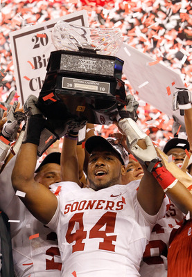 ARLINGTON, TX - DECEMBER 04:  Defensive end Jeremy Beal #44 of the Oklahoma Sooners celebrates with the Big 12 Championship Trophy after the Sooners beat the Nebraska Cornhuskers 23-20 at Cowboys Stadium on December 4, 2010 in Arlington, Texas.  (Photo by