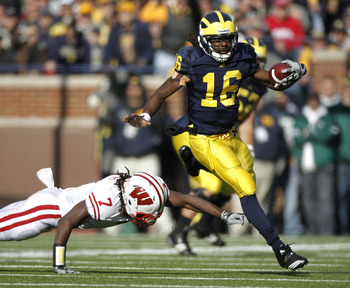 ANN ARBOR, MI - NOVEMBER 20: Denard Robinson #16 of the Michigan Wolverines gets around the tackle of Aaron Henry #7 of the Wisconsin Badgers at Michigan Stadium on November 20, 2010 in Ann Arbor, Michigan.  (Photo by Gregory Shamus/Getty Images)