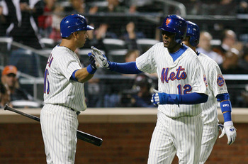 NEW YORK - SEPTEMBER 15:  Joaquin Arias #12 (C) of the New York Mets celebrates with Carlos Beltran #15 (L) after scoring a run in the fourth inning against the Pittsburgh Pirates on September 15, 2010 at Citi Field in the Flushing neighborhood of the Que