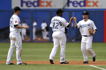 TORONTO - SEPTEMBER 23:   Lyle Overbay #35, Edwin Encarnacion #12 and Aaron Hill #2 of the Toronto Blue Jays celebrate the teams win over the Seattle Mariners during game action September 23, 2010 at Rogers Centre in Toronto, Ontario, Canada. (Photo by Br