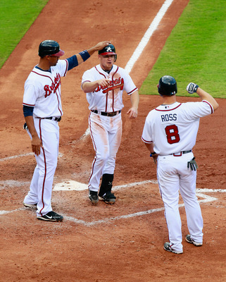 ATLANTA - SEPTEMBER 29:  Brooks Conrad #26 of the Atlanta Braves celebrates with Derrek Lee #27 and David Ross #8 after hitting a three-run homer in the third inning against the Florida Marlins at Turner Field on September 29, 2010 in Atlanta, Georgia.  (