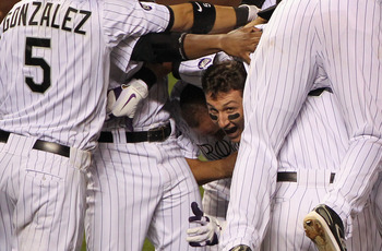 DENVER - SEPTEMBER 25:  Troy Tulowitzki #2 of the Colorado Rockies emerges from the celebration after he hit the game RBI double to score Carlos Gonzalez #5 against the San Francisco Giants in the 10th inning at Coors Field on September 25, 2010 in Denver
