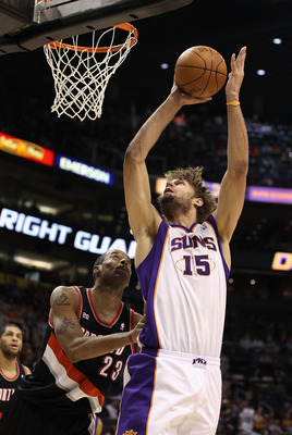 PHOENIX, AZ - JANUARY 14:  Robin Lopez #15 of the Phoenix Suns puts up a shot over Marcus Camby #23 of the Portland Trail Blazers during the NBA game at US Airways Center on January 14, 2011 in Phoenix, Arizona.  The Suns defeated the 115-111.  NOTE TO US
