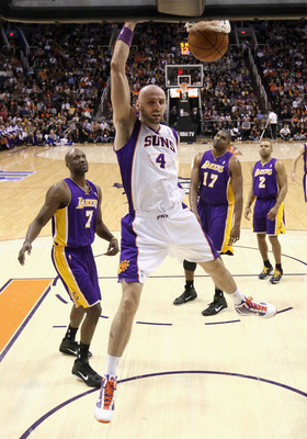 PHOENIX - JANUARY 05: Marcin Gortat #4 of the Phoenix Suns slam dunks the ball past Lamar Odom #7 of the Los Angeles Lakers during the NBA game at US Airways Center on January 5, 2011 in Phoenix, Arizona. The Lakers defeated the Suns 99-95. NOTE TO USER: