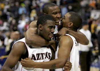 DENVER - MARCH 11:  Marcus Slaughter #42 hugs Brandon Heath #1 and John Sharper #15 of the San Diego State University Aztecs after defeating the Wyoming Cowboys 69-64 in the championship of the Mountain West Conference Basketball Tournament on March 11, 2