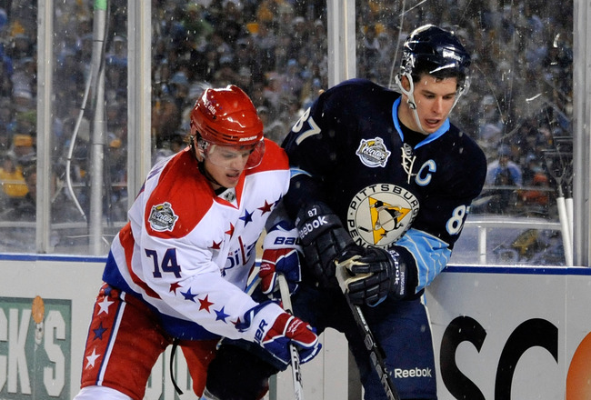 PITTSBURGH, PA - JANUARY 01:  Sidney Crosby #87 of the Pittsburgh Penguins battles for the puck against John Carlson #74 of the Washington Capitals during the 2011 NHL Bridgestone Winter Classic at Heinz Field on January 1, 2011 in Pittsburgh, Pennsylvani