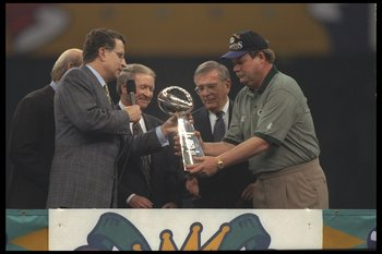 26 Jan 1997:  Head coach Mike Holmgren of the Green Bay Packers (right) receives the Vince Lombardi trophy from NFL commissioner Paul Tagliabue (left) after the Packers beat the New England Patriots 35-21 to win Super Bowl XXXI at the Louisiana Superdome
