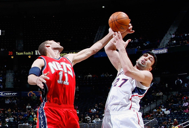 ATLANTA, GA - DECEMBER 07:  Zaza Pachulia #27 of the Atlanta Hawks battles for a rebound against Brook Lopez #11 of the New Jersey Nets at Philips Arena on December 7, 2010 in Atlanta, Georgia.  NOTE TO USER: User expressly acknowledges and agrees that, b