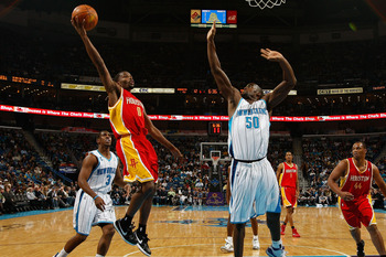 NEW ORLEANS, LA - JANUARY 02:  Aaron Brooks #0 of the Houston Rockets makes a shot over Emeka Okafor #50 of the New Orleans Hornets at the New Orleans Arena on January 2, 2010 in New Orleans, Louisiana.  NOTE TO USER: User expressly acknowledges and agree