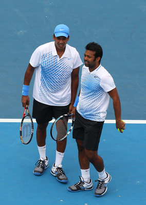 MELBOURNE, AUSTRALIA - JANUARY 22:  Mahesh Bhupathi of India (L) talks tactics with partner Leander Paes also of India in his second round doubles match against Felilciano Lopez of Spain and Juan Monaco of Argentina during day six of the 2011 Australian O