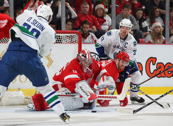 DETROIT, MI - DECEMBER 22:  Henrik Sedin #33 and Daniel Sedin #22 of the Vancouver Canucks press for a goal against Henrik Zetterberg #40 and Jimmy Howard #35 of the Detroit Red Wings in a game on December 22, 2010 at the Joe Louis Arena in Detroit, Michi