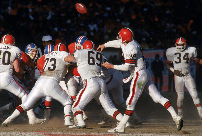 DENVER - JANUARY 17:  Quarterback Bernie Kosar #19 of the Cleveland Browns releases the ball behind strong protection during the 1987 AFC Championship game against the Denver Broncos at Mile High Stadium on January 17, 1988 in Denver, Colorado.  The Bronc