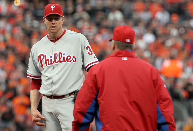 SAN FRANCISCO - OCTOBER 21:  (R-L) Pitching coach Rich Dubee of the Philadelphia Phillies heads to the mound to speak with Roy Halladay #34 in the first inning of Game Five of the NLCS against the San Francisco Giants during the 2010 MLB Playoffs at AT&T