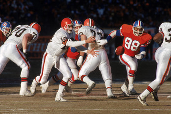 DENVER - JANUARY 17:  Quarterback Bernie Kosar #19 of the Cleveland Browns pitches the ball to his right as linebacker Ricky Hunley #98 of the Denver Broncos approaches during the 1987 AFC Championship game at Mile High Stadium on January 17, 1988 in Denv