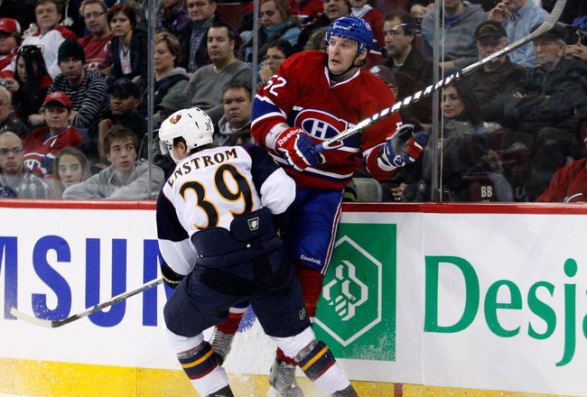 MONTREAL, CANADA - JANUARY 2:  Tobias Enstrom #39 of the Atlanta Thrashers body checks Mathieu Darche #52 of the Montreal Canadiens during the NHL game at the Bell Centre on January 2, 2011 in Montreal, Quebec, Canada.  The Thrashers defeated the Canadien