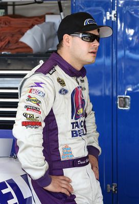 AVONDALE, AZ - NOVEMBER 12:  David Gilliland, driver of the #37 Taco Bell Ford, stands in the garage during practice for the NASCAR Sprint Cup Series Kobalt Tools 500 at Phoenix International Raceway on November 12, 2010 in Avondale, Arizona.  (Photo by C