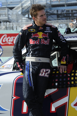 HOMESTEAD, FL - NOVEMBER 19:  Scott Speed, driver of the #82 Red Bull Toyota, leans on his car during qualifying for the NASCAR Sprint Cup Series Ford 400 at Homestead-Miami Speedway on November 19, 2010 in Homestead, Florida.  (Photo by John Harrelson/Ge