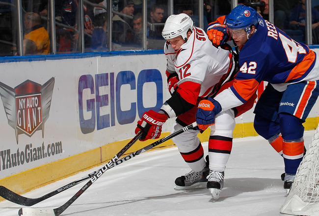 UNIONDALE, NY - JANUARY 26:  Eric Staal #12 of the Carolina Hurricanes is checked by Dylan Reese #42 of the New York Islanders during the first period of an NHL hockey game at the Nassau Coliseum on January 26, 2011 in Uniondale, New York.  (Photo by Paul