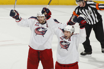 SUNRISE, FL - JANUARY 19: RJ Umberger #18 (R) and Rick Nash #61 of the Columbus Blue Jackets raise their sticks and celebrate Nash's winning goal against the Florida Panthers on January 19, 2011 at the BankAtlantic Center in Sunrise, Florida. The Blue Jac