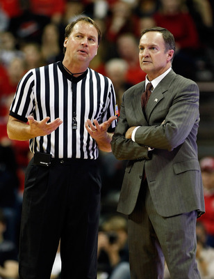LAS VEGAS, NV - JANUARY 05:  Referee John Higgins (L) talks to head coach Lon Kruger of the UNLV Rebels during the team's game against the Brigham Young University Cougars at the Thomas & Mack Center January 5, 2011 in Las Vegas, Nevada. BYU won 89-77.  (