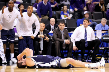 OKLAHOMA CITY - MARCH 20:  Noah Hartsock #34 of the Brigham Young Cougars lies on the court with his hands on his head as his teammates react on the bench against the Kansas State Wildcats during the second round of the 2010 NCAA men's basketball tourname