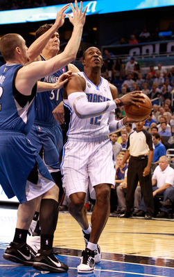 ORLANDO, FL - NOVEMBER 03:  Dwight Howard #12 of the Orlando Migic drives against Darko Milicic #31 and Kevin Love #42 of the Minnesota Timberwolves during the game at Amway Arena on November 3, 2010 in Orlando, Florida.  NOTE TO USER: User expressly ackn