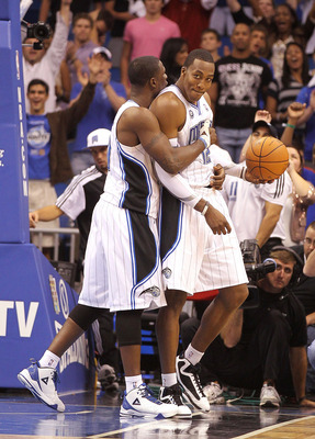 ORLANDO, FL - NOVEMBER 24:  Dwight Howard #12 of the Orlando Magic is hugged by Brandon Bass #30 after winning a game against the Miami Heat at Amway Arena on November 24, 2010 in Orlando, Florida. NOTE TO USER: User expressly acknowledges and agrees that
