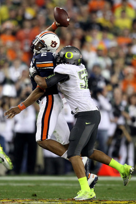 GLENDALE, AZ - JANUARY 10:  Cameron Newton #2 of the Auburn Tigers tries to pass as Kenny Rowe #58 of the Oregon Ducks tries to tackle him during the Tostitos BCS National Championship Game at University of Phoenix Stadium on January 10, 2011 in Glendale,