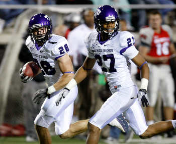 LAS VEGAS - OCTOBER 30:  Colin Jones #28 of the Texas Christian University Horned Frogs runs for a 30-yard touchdown after making an interception against the UNLV Rebels as his teammate Jason Teague #27 runs with him during the second quarter of their gam