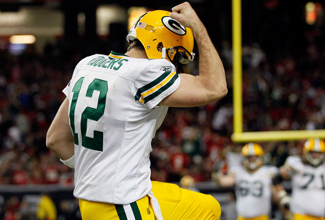 ATLANTA, GA - JANUARY 15:  Aaron Rodgers #12 of the Green Bay Packers reacts after he threw a 7-yard touchdown to John Kuhn #30 in the third quarter against the Atlanta Falcons during their 2011 NFC divisional playoff game at Georgia Dome on January 15, 2