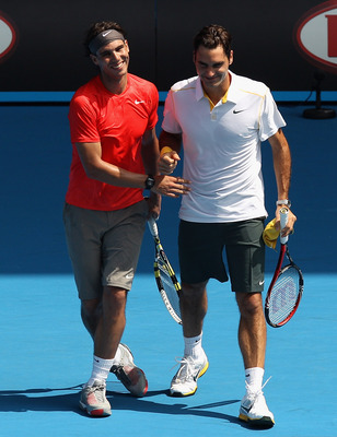 MELBOURNE, AUSTRALIA - JANUARY 16:  Rafael Nadal of Spain and Roger Federer of Switzerland celebrate a point during the 'Rally For Relief' charity exhibition match ahead of the 2011 Australian Open at Melbourne Park on January 16, 2011 in Melbourne, Austr