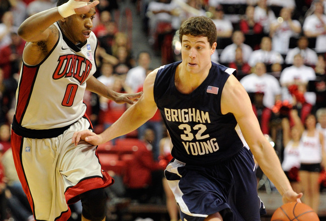 LAS VEGAS, NV - JANUARY 05:   Jimmer Fredette #32 of the Brigham Young University Cougars drives against Oscar Bellfield #0 of the UNLV Rebels during their game at the Thomas & Mack Center January 5, 2011 in Las Vegas, Nevada. BYU won 89-77.  (Photo by Et