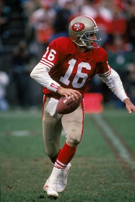 SAN FRANCISCO - JANUARY 12:  Quarterback Joe Montana #16 of the San Francisco 49ers runs with the ball as he looks down field for a receiver during the 1990 NFC Divisional Playoff game against the Washington Redskins at Candlestick Park on January 12, 199