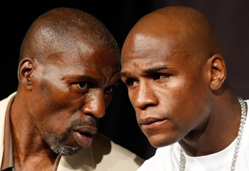 LAS VEGAS - SEPTEMBER 16:  Boxer Floyd Mayweather Jr. (R) and his uncle and trainer Roger Mayweather confer during the final news conference for their bout against Juan Manuel Marquez at the MGM Grand Hotel/Casino September 16, 2009 in Las Vegas, Nevada.