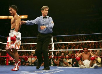 LAS VEGAS - NOVEMBER 18:  (L-R) Manny Pacquiao of the Philippines is directed to his corner by referee Vic Drakulich as Erik Morales of Mexico is knocked down for the second time in round three during their super featherweight bout at the Thomas & Mack Ce