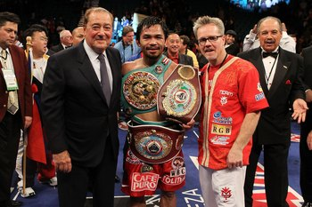 LAS VEGAS - NOVEMBER 14:  (L-R) Promoter Bob Arum, boxer Manny Pacquiao and trainer Freddie Roach celebrate Pacquiao's 12 round TKO victory against Miguel Cotto during their WBO welterweight title fight at the MGM Grand Garden Arena on November 14, 2009 i