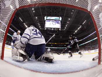 TAMPA, FL - JANUARY 25: James Reimer #34 of the Toronto Maple Leafs makes a save as Teddy Purcell #16 of the Tampa Bay Lightning crashes the net at St. Pete Times Forum on January 25, 2011 in Tampa, Florida. The Lightning defeated the Leafs 2-0. (Photo by