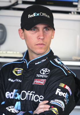 DAYTONA BEACH, FL - JANUARY 20:  Denny Hamlin, driver of the #11 FedEx Toyota waits in the garage during testing at Daytona International Speedway on January 20, 2011 in Daytona Beach, Florida.  (Photo by Jerry Markland/Getty Images for NASCAR)