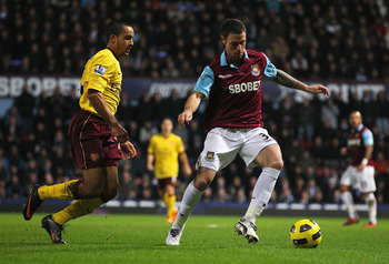 LONDON, ENGLAND - JANUARY 15: Wayne Bridge of West Ham United is closed down by Theo Walcott of Arsenal during the Barclays Premier League match between West Ham United and Arsenal at the Boleyn Ground on January 15, 2011 in London, England.  (Photo by Cl