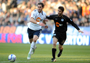 BOLTON, ENGLAND - JANUARY 29: Johan Elmander of Bolton Wanderers competes with Adrian Lopez of Wigan Athletic during the FA Cup sponsored by E.ON 4th Round match between Bolton Wanderers and Wigan Athletic at the Reebok Stadium on January 29, 2011 in Bolt