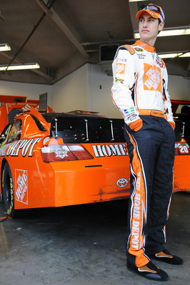 DAYTONA BEACH, FL - JANUARY 22:  Joey Logano, driver of the #20 Home Depot Toyota, stands by his car in the garage area during testing at Daytona International Speedway on January 22, 2011 in Daytona Beach, Florida.  (Photo by Jared C. Tilton/Getty Images