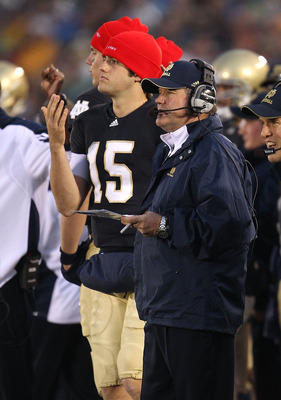 SOUTH BEND, IN - NOVEMBER 13: Head coach Brian Kelly of the Notre Dame Fighting Irish watches as his team takes on the Utah Utes while Brian Castello #15 signals a play at Notre Dame Stadium on November 13, 2010 in South Bend, Indiana. Notre Dame defeated