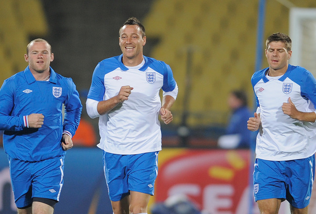 RUSTENBURG, SOUTH AFRICA - JUNE 11:  Wayne Rooney and John Terry share a joke as Steven Gerrard looks on during the England training session at the Royal Bafokeng Stadium on June 11, 2010 in Rustenburg, South Africa.  (Photo by Michael Regan/Getty Images)
