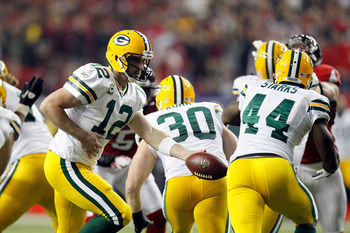 ATLANTA, GA - JANUARY 15:  Quarterback Aaron Rodgers #12 of the Green Bay Packers turns to hand the ball off to James Starks #44 against the Atlanta Falcons during their 2011 NFC divisional playoff game at Georgia Dome on January 15, 2011 in Atlanta, Geor