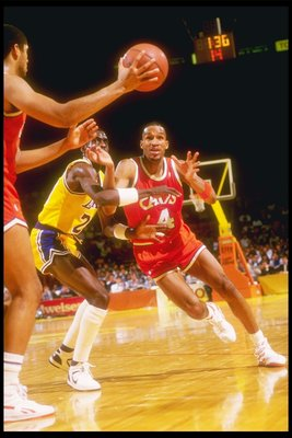 1986-1987:  Center Brad Daugherty (left) of the Cleveland Cavaliers makes a pass to team player guard  Ron Harper over the defense of the Los Angeles Lakers during a game at The Forum in Inglewood, California. Mandatory Credit: Stephen Dunn  /Allsport
