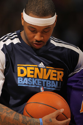 DENVER, CO - JANUARY 21:  Carmelo Anthony #15 of the Denver Nuggets looks on as he warms up for the second half against the Los Angeles Lakers at the Pepsi Center on January 21, 2011 in Denver, Colorado. The Lakers defeated the Nuggets 107-97. NOTE TO USE
