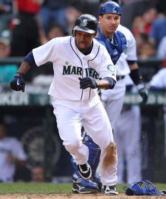SEATTLE - SEPTEMBER 19:  Chone Figgins #9 of the Seattle Mariners runs back to touch home plate after missing it on his initial slide against catcher Matt Treanor #20 of the Texas Rangers on a double by Franklin Gutierrez #21 in the sixth inning at Safeco