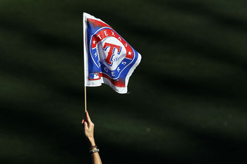 ARLINGTON, TX - OCTOBER 30:  A fan of the Texas Rangers holds up a Rangers' flag against the San Francisco Giants in Game Three of the 2010 MLB World Series at Rangers Ballpark in Arlington on October 30, 2010 in Arlington, Texas.  (Photo by Ronald Martin